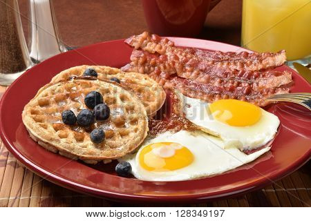 Bacon, fried eggs and waffles for breakfast