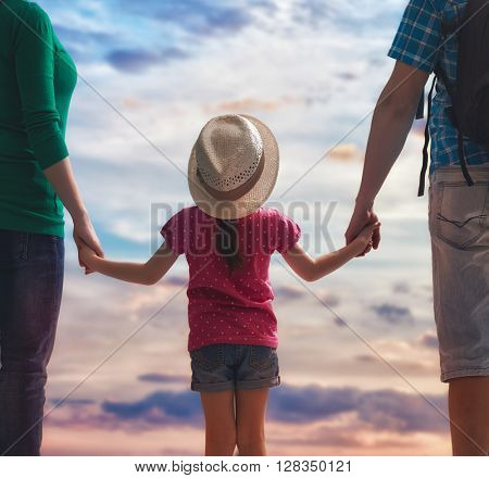 happy family at sunset. mother, father and daughter having fun and playing in nature. family travels.