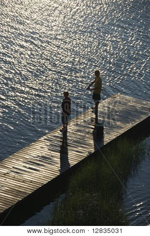 Birds eye view of two teenage boys fishing from dock at Bald Head Island, North Carolina.