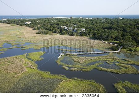 Aerial of marsh with dock and pier and houses in background in Bald Head Island, North Carolina.
