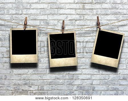 photo on rope with clothespins on a background of a brick wall