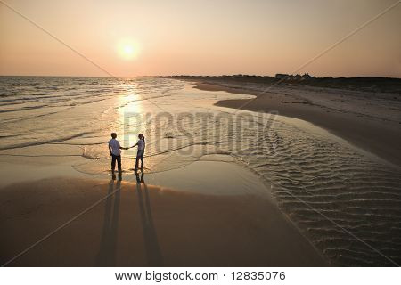 Aerial view of romantic couple standing on beach holding hands on Bald Head Island, North Carolina.