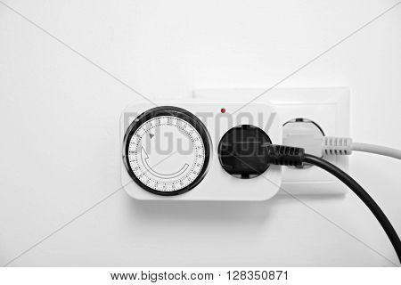 Power plug with timer switch on white wall background