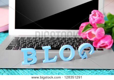 Laptop with word BLOG and fresh tulips on blue mat closeup