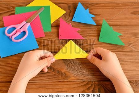 Origami colorful fish, paper sheets, scissors. Child holds paper sheet in his hands and making origami fish. Brown wooden table
