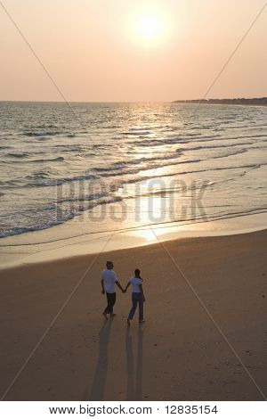 Aerial of couple holding hands and walking on beach on Bald Head Island, North Carolina.