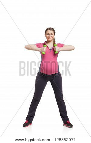 Young pregnant woman making exercise with dumb bells isotated on white