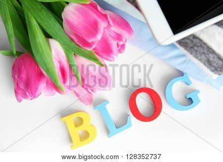Word BLOG with stack of clothes, mobile phone and bouquet of fresh tulips on table, top view