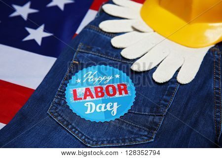 Labor day concept. Yellow helmet, gloves and jeans on US flag background