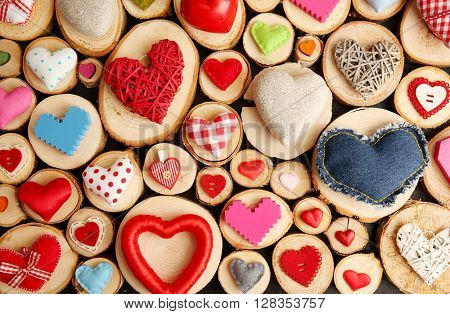 Set of different craft hearts on wooden logs