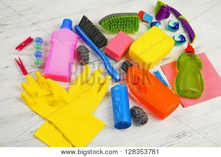 Cleaning set with tools and products on light wooden background