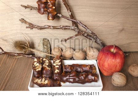 Sliced sweet sausage with nuts and a hanging sweet sausage on the branches
