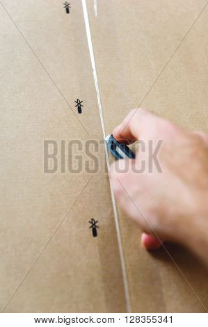 Man hand cutting a cardboard box sharp steel box cutter knife to open it.