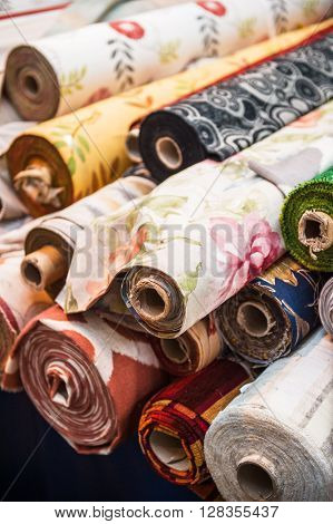 Rolls of tissues at traditional textile covered market with multiple different colors and textures