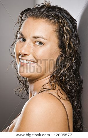 Portrait of pretty young adult Caucasian brunette female smiling and looking at viewer.