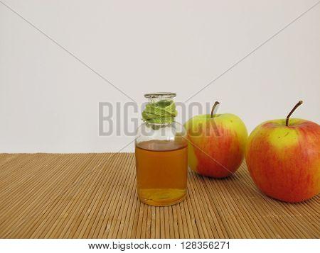 Apple cider vinegar in bottle and apples