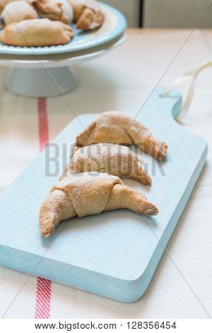Freshly baked short crust pastry crescent rolls topped with ice sugar on a colorful plate and a wooden cutting board