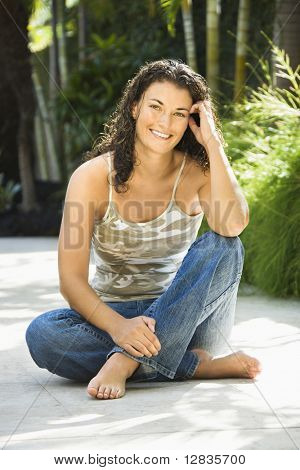 Portrait of pretty young adult Caucasian brunette woman sitting with elbow on knee smiling and looking at viewer.