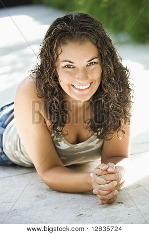 Pretty young adult Caucasian brunette woman lying on walkway leaning on elbows with hands clasped.
