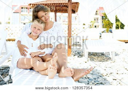Luxury resort happy family relaxing . Mother and daughter sitting on deckchair of beach resort . Summer vacation idea.