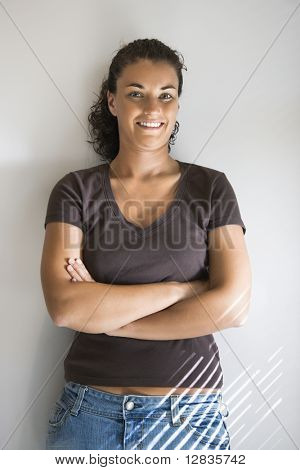 Portrait of pretty young adult Caucasian brunette female with arms crossed smiling and looking at viewer.