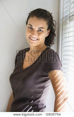 Portrait of smiling pretty young adult Caucasian brunette female standing and looking at viewer.