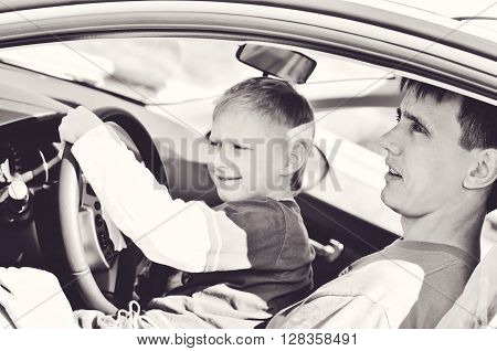 Father and son are sitting in a car