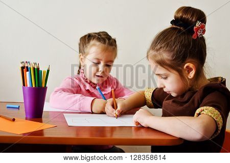 two preschool girls are drawing at the table