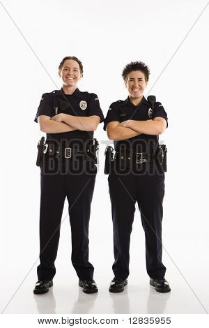 Portrait of two mid adult Caucasian policewomen standing with arms crossed looking at viewer smiling.