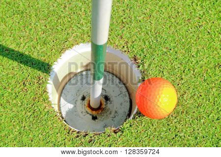 Aerial view of golf hole and orange golf ball on green grass golf course.