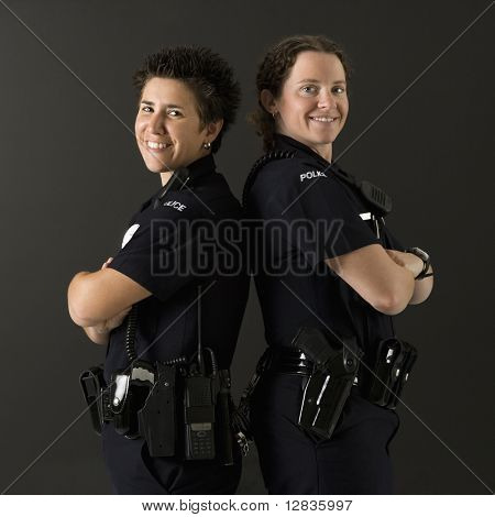 Portrait of two mid adult Caucasian policewomen standing back to back looking over their shoulders smiling at viewer.