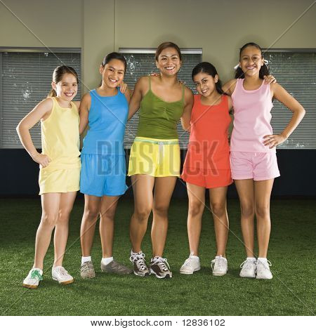 Portrait of four girls and one woman standing together smiling in indoor gym.