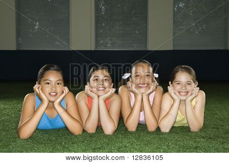 Four multiethnic girls lying on ground in indoor gym with heads on hands smiling.