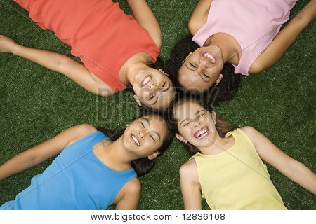 Above view of four girls lying on artificial grass with heads together laughing.