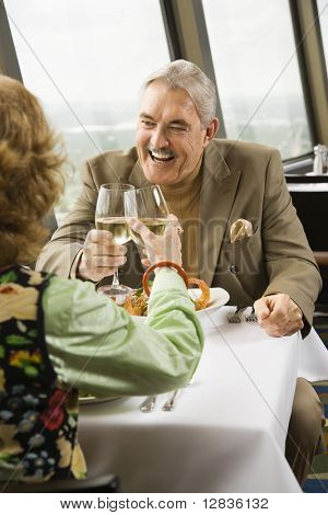 Mature couple dining and toasting in fancy restaurant by window with rooftop view of urban landscape.