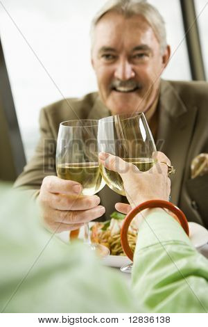 Mature couple dining and toasting in fancy restaurant.