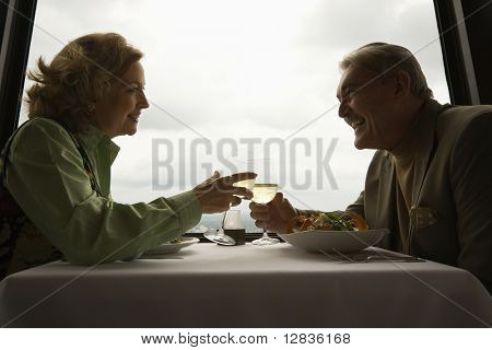 Caucasian mature couple at nice restaurant drinking wine and talking and laughing.
