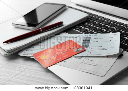 Laptop with mobile phone, credit card and flight tickets on light wooden table