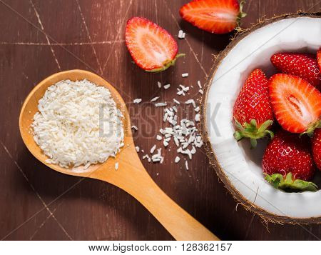 Half coconut with strawberries and shredded coconut on dark brown rustic wooden background. Closeup
