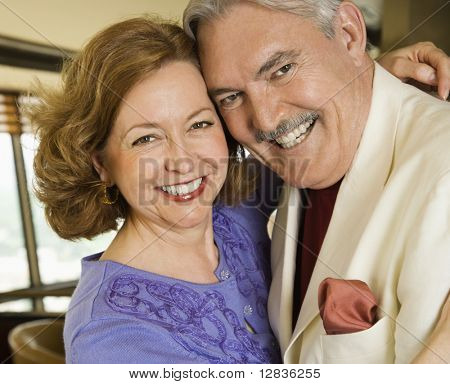 Portrait of mature Caucasian couple embracing and smiling.
