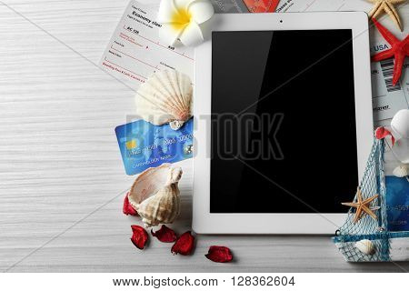 Tablet with credit cards and flight tickets for vacation on light wooden table