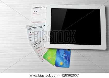 Tablet with credit cards and flight tickets on light wooden table
