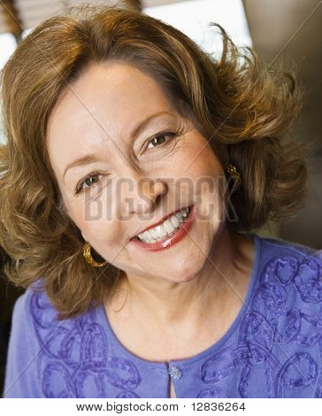 Head and shoulder portrait of smiling middle aged Caucasian woman.