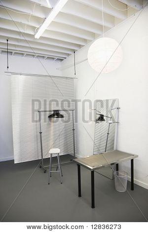 Arbeitsbereich mit Tisch, Stuhl, Spiegel, Kleidung-Rack und Raum-Teiler.