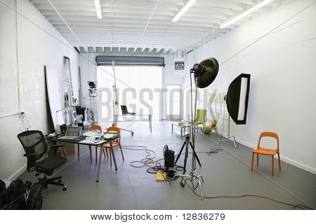 Interior of  photography studio with lights and various equipment and props.