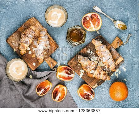 Traditional Italian style home breakfast. Latte in glasses, almond croissants on rustic wooden boards and red bloody Sicilian oranges over concrete textured table, top view, horizontal