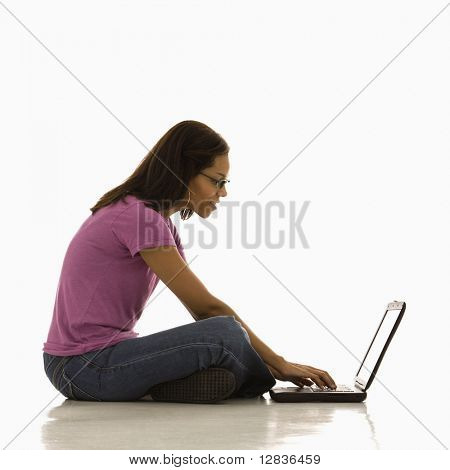 Side view of mid adult African American woman sitting on floor using laptop.