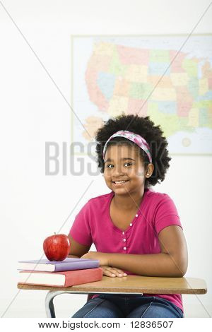 African American girl sitting in school desk smiling at viewer.