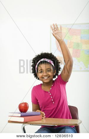 African American girl sitting in school desk raising hand and smiling at viewer.