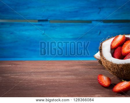 Half coconut with strawberries and shredded coconut on bright blue and brown rustic wooden background. Copy space